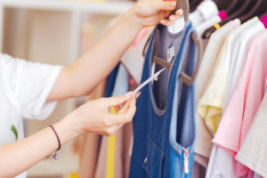difference between being frugal and cheap – checking price tags on clothing