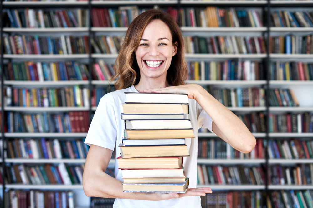 girl holding a stack of books, hosting a book swap as a creating fundraising idea