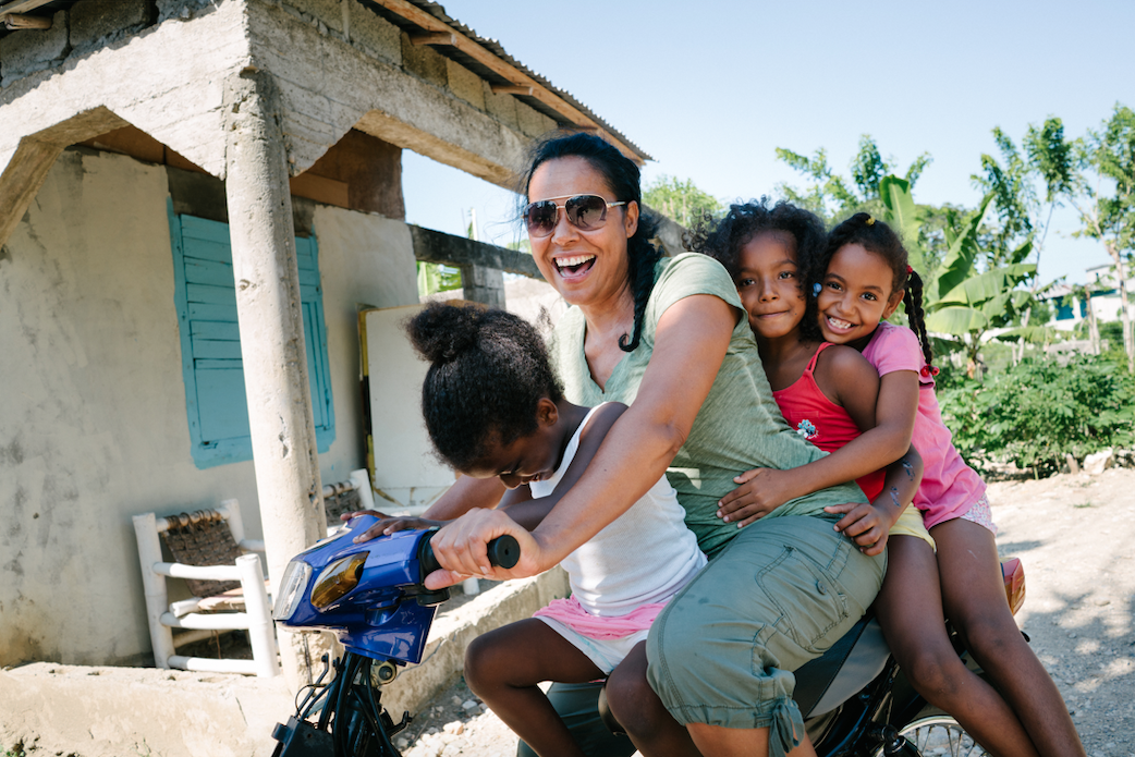 woman on a bike with children, giving back while on vacation