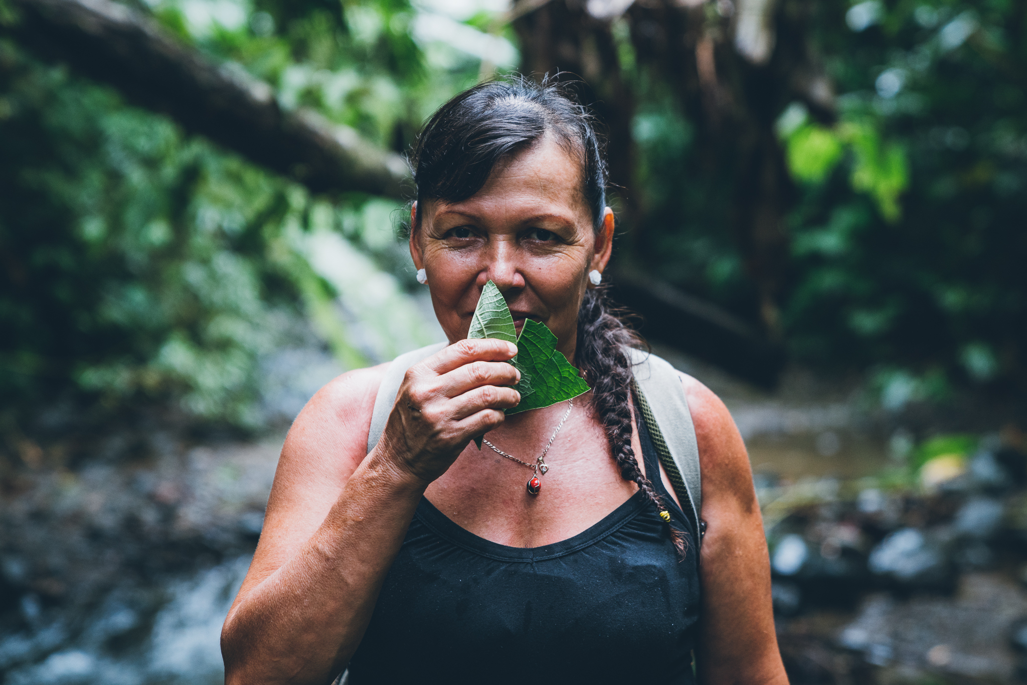 woman in the rainforest with leaves in front of her face