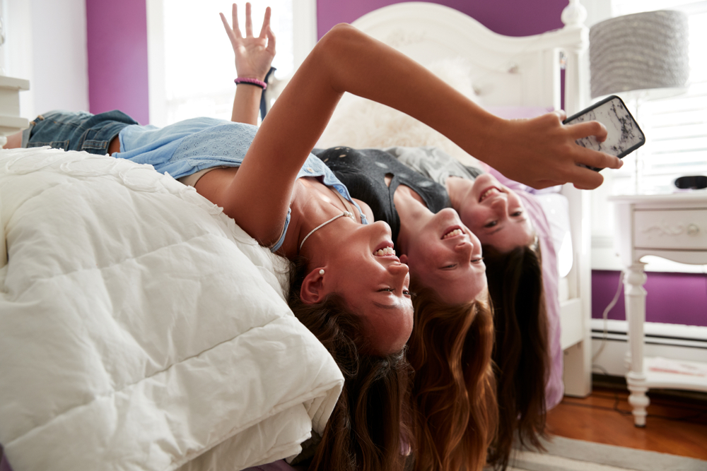 three teenage girls taking a selfie in a bedroom - real life with teenagers