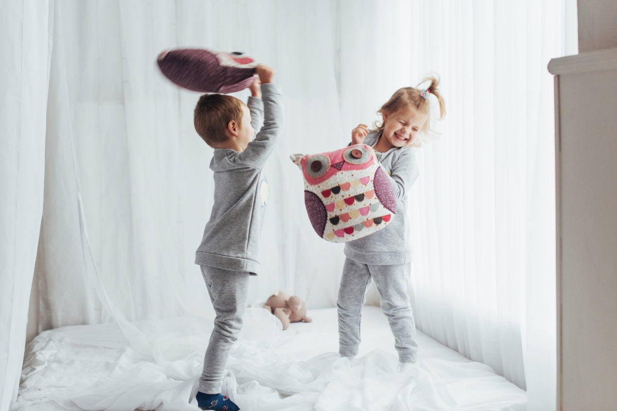 young siblings having a pillow fight