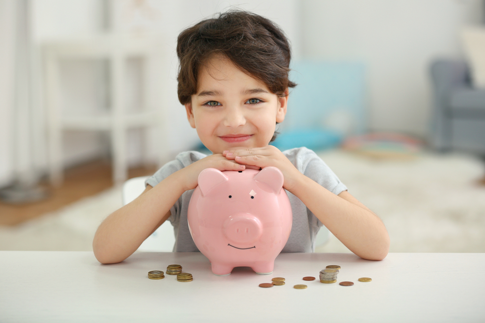 little boy sitting with his piggy bank learning about finances
