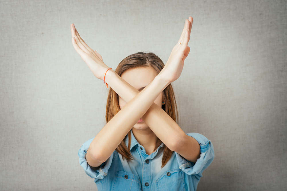 woman holding her arms up in an X in front of her face