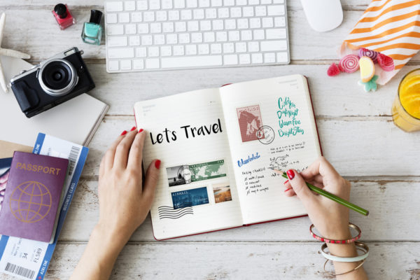 person writing in a travel diary surrounded by items to help her document travels