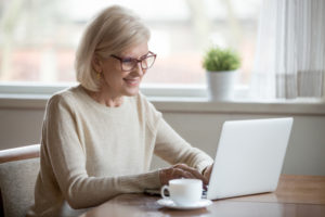 retired woman writing an email to a friend about being 65 and retired