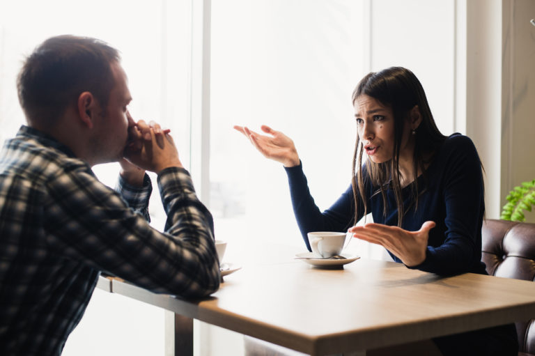 couple arguing at a table, trying to manage conflict