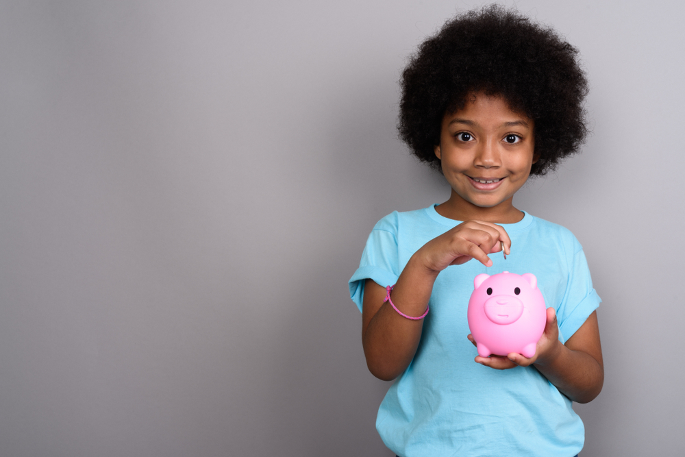 little girl in front of a grey background putting coins into a pink piggy bank - teaching kids about money