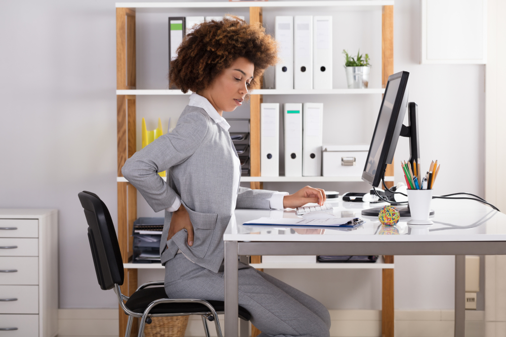 girl sitting at her desk holding her lower back considering how to improve posture