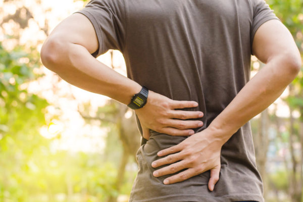 man on a run holding his lower back considering how to improve posture