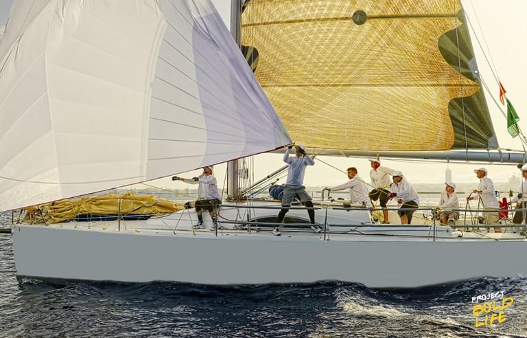 sailing team on the ocean racing a sailboat