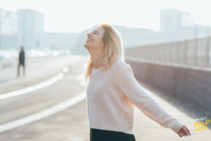 woman looking carefree with her arms open looking at the sky - living in the present