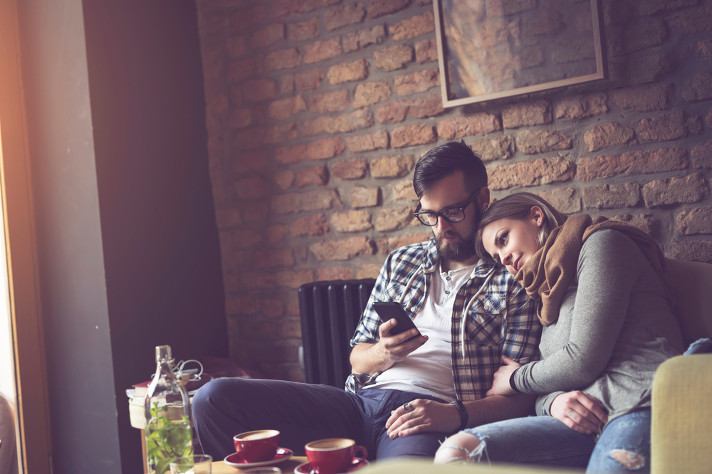 """couple sitting on a couch, man on his phone while his spouse watches; """"phubbing""""; cell phones and relationship problems"""
