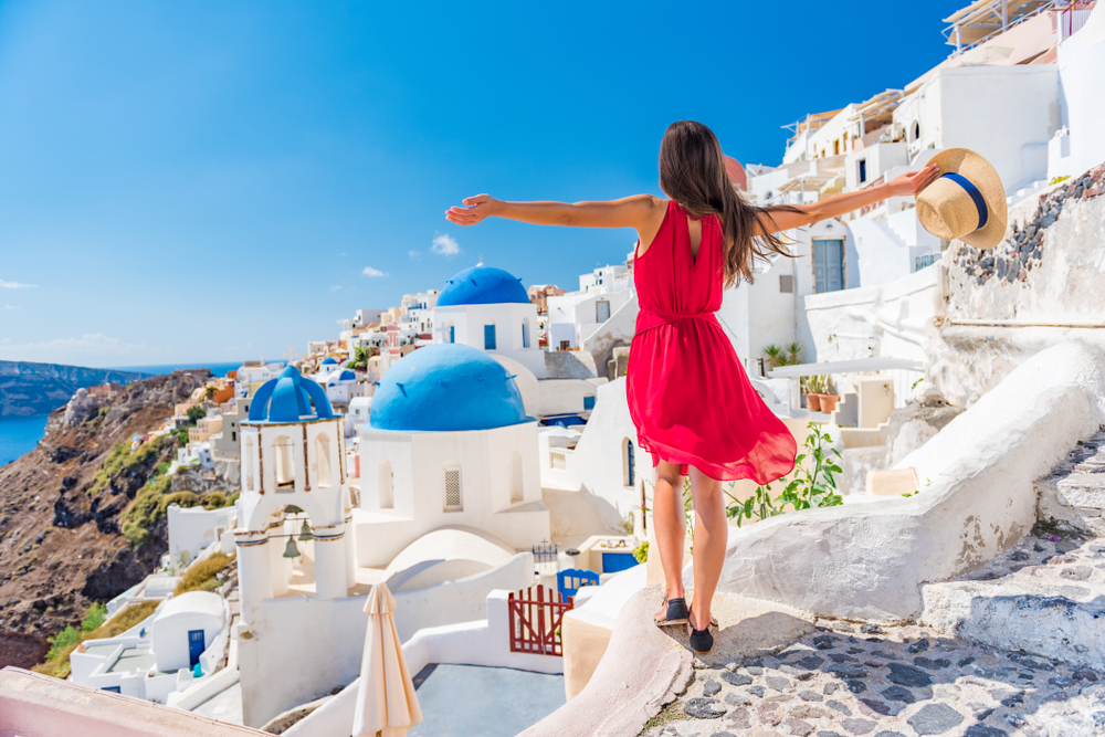 Woman overlooking the city of Oia in Santorini, Greece - travel bucket list destination
