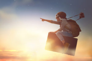 kid flying in the sky on a suitcase - what do our dreams mean?