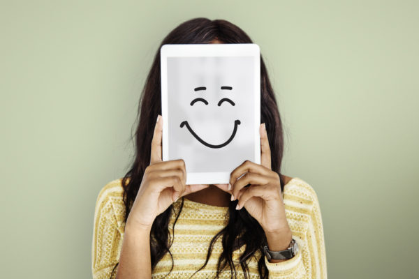 woman holding up a tablet with a happy face drawn on it to show feelings and emotions