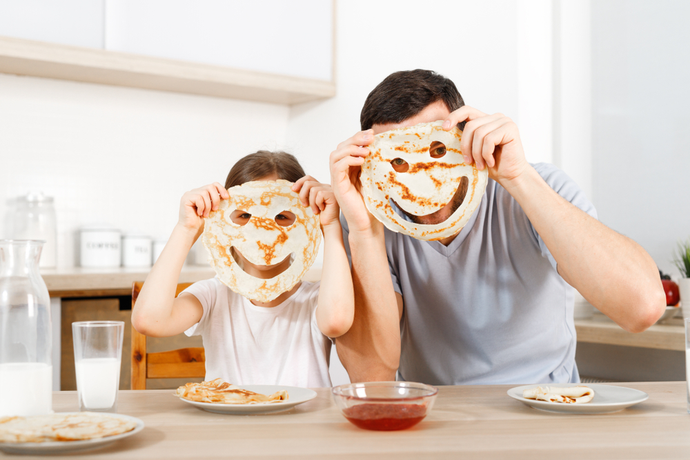 father and son holding up pancake smiley faces