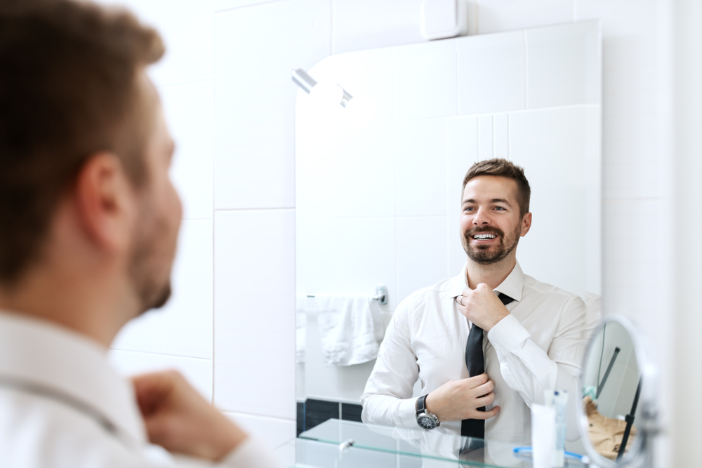 man getting dressed for interview wearing appropriate interview attire