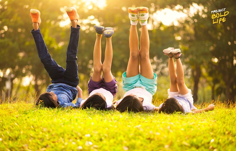 kids laying in the grass with their legs in the air - childlike wonder