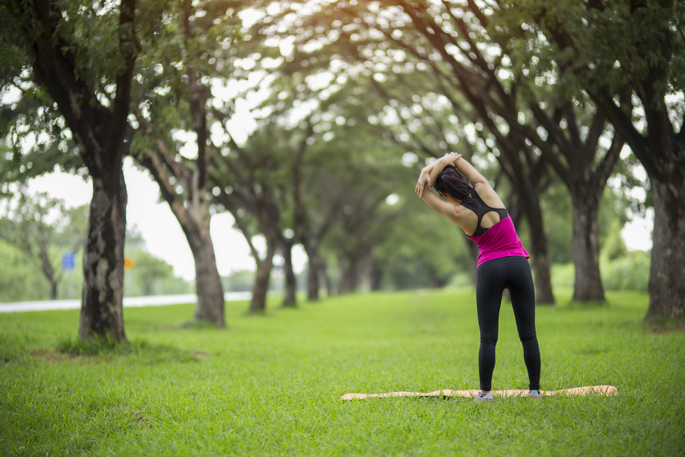 girl doing light exercise and stretches in park