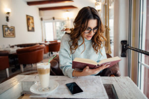 young woman reading in a cafe to complete list of Books to Read Before You're 30