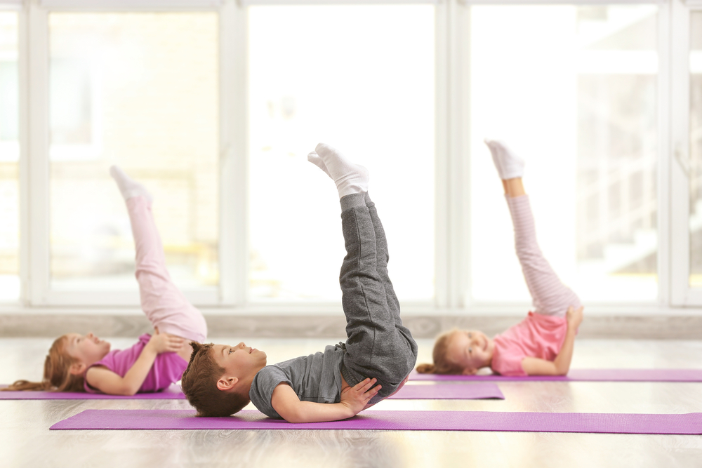three kids practicing yoga on mats