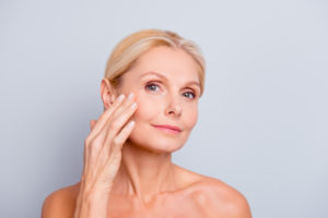 middle-aged woman with beautiful skin using anti-aging skin care