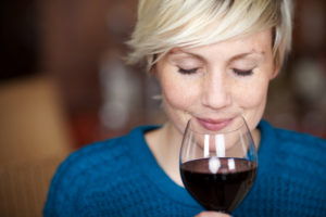 woman with her eyes closed smelling a big glass of wine