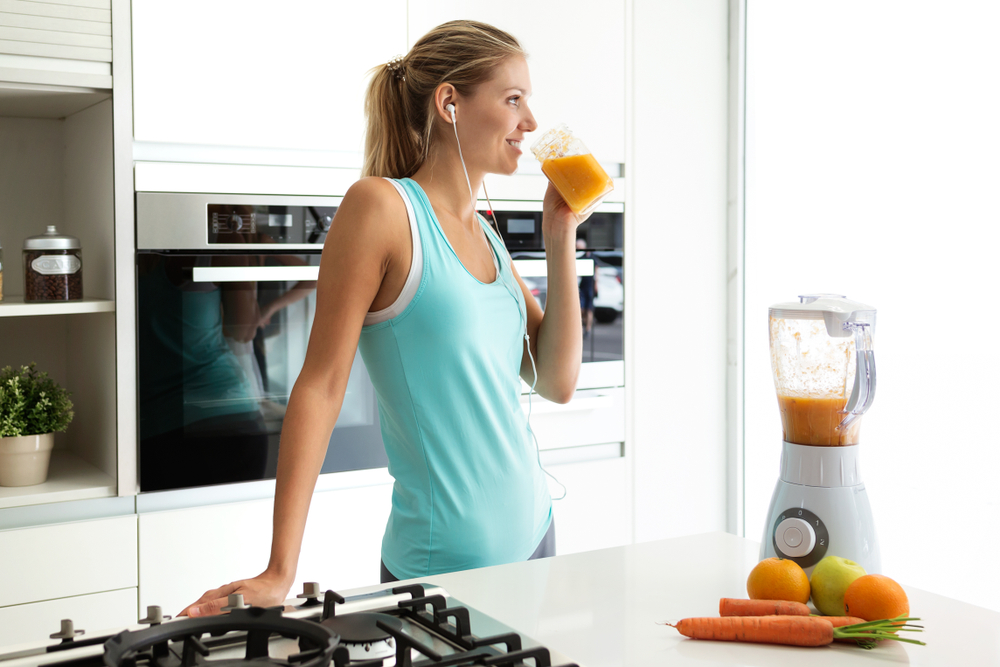 woman drinking juice in her kitchen after running - developing a morning routine