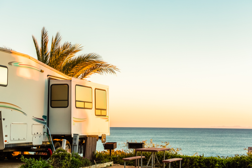 recreational vehicle used by millennial generation parked by the ocean