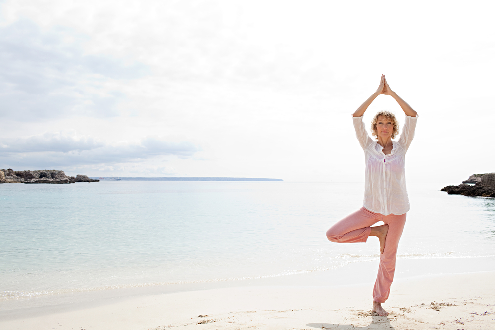 woman balancing on one leg on the beach - representing benefits of stem cells for health