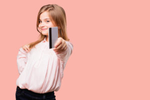 girl holding her kids debit card towards the camera with pink background