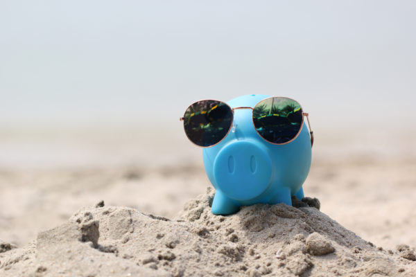 piggy bank in the sand with sunglasses symbolizing preparing for retirement