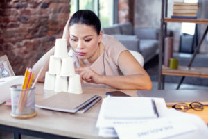 woman building a pyramid of cups to procrastinate what needs to get done