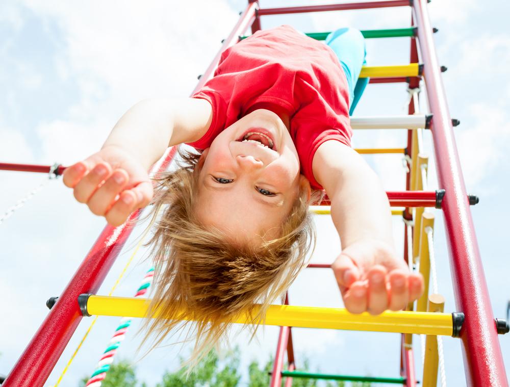 risk taker hanging upside down from monkey bars