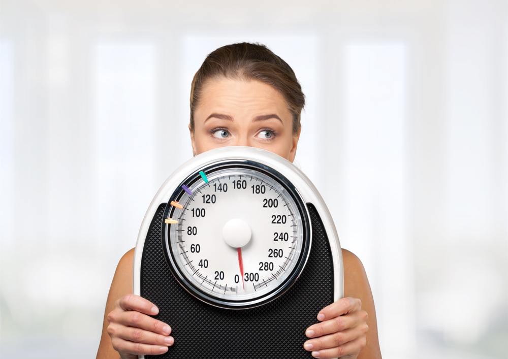 woman holding up a scale in front of her face, thinking about stress and weight loss