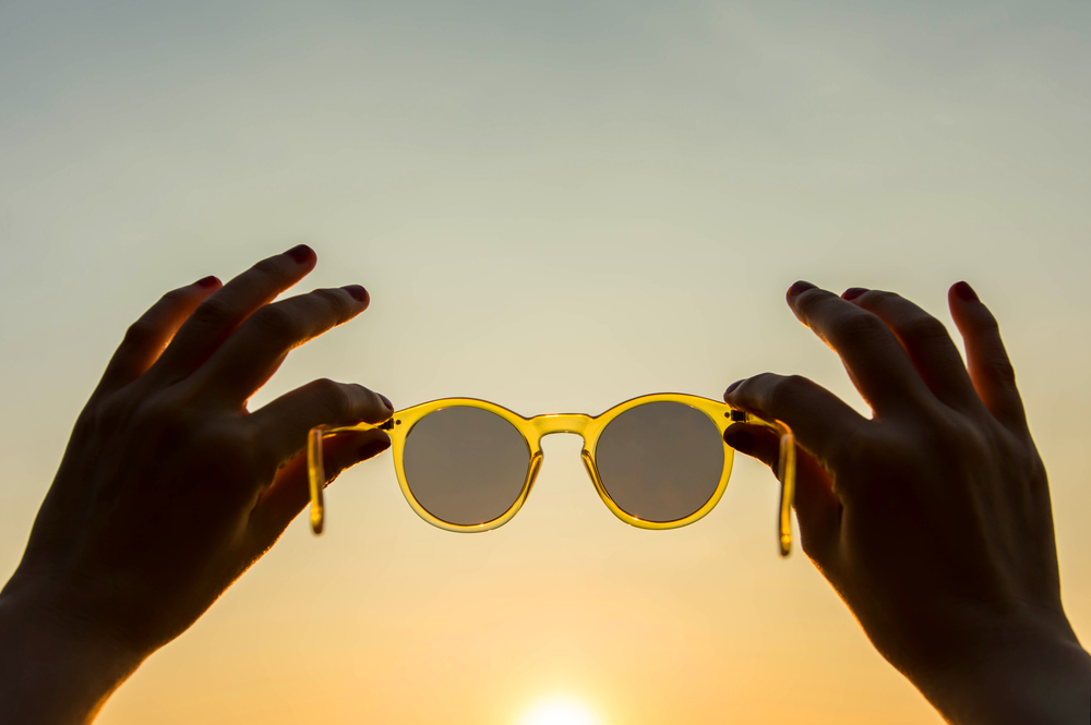 hands holding up sunglasses in front of the sun