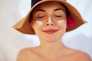 girl in a hat wearing skin cream