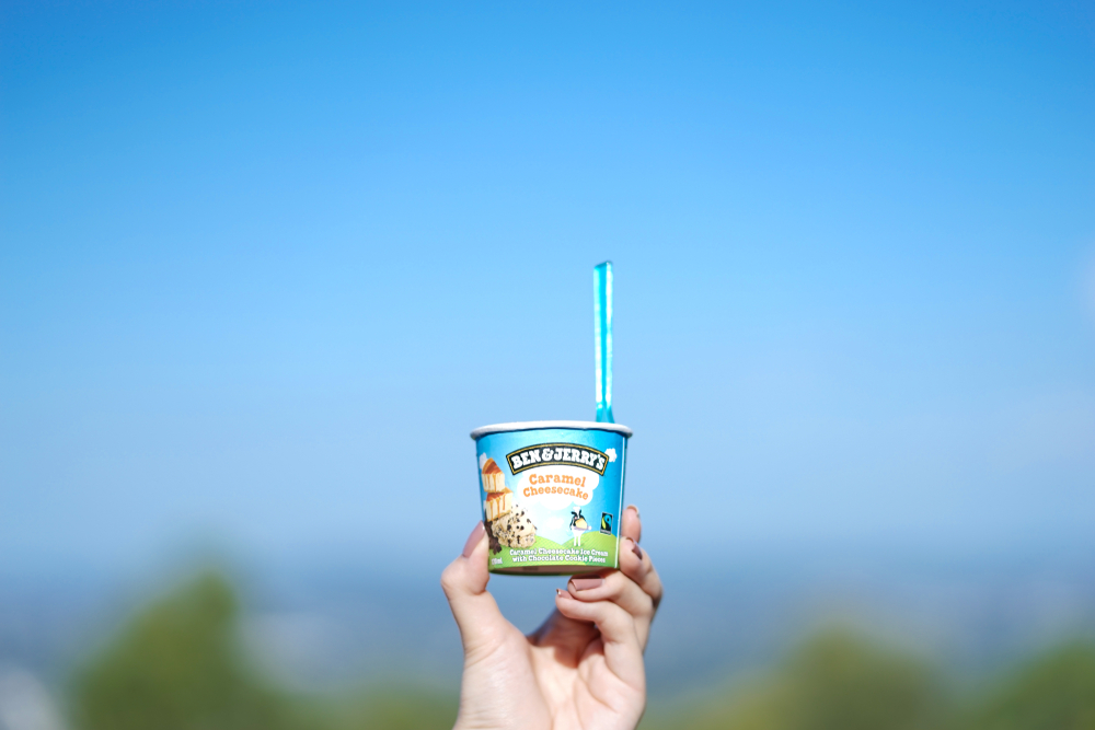 a hand holding a cup of ben & jerry's ice cream