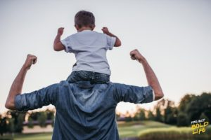 father and son relationships - dad carrying son on his shoulders showing muscles