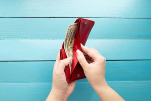 opening a wallet full of money in front of blue background