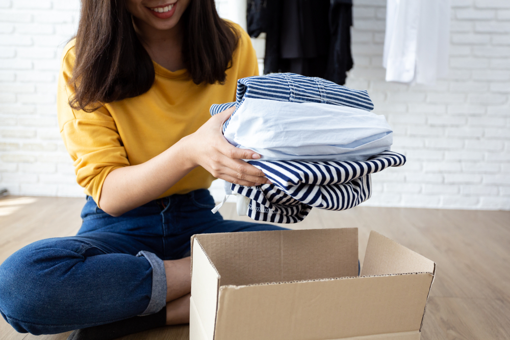 millennial girl giving clothes to charity