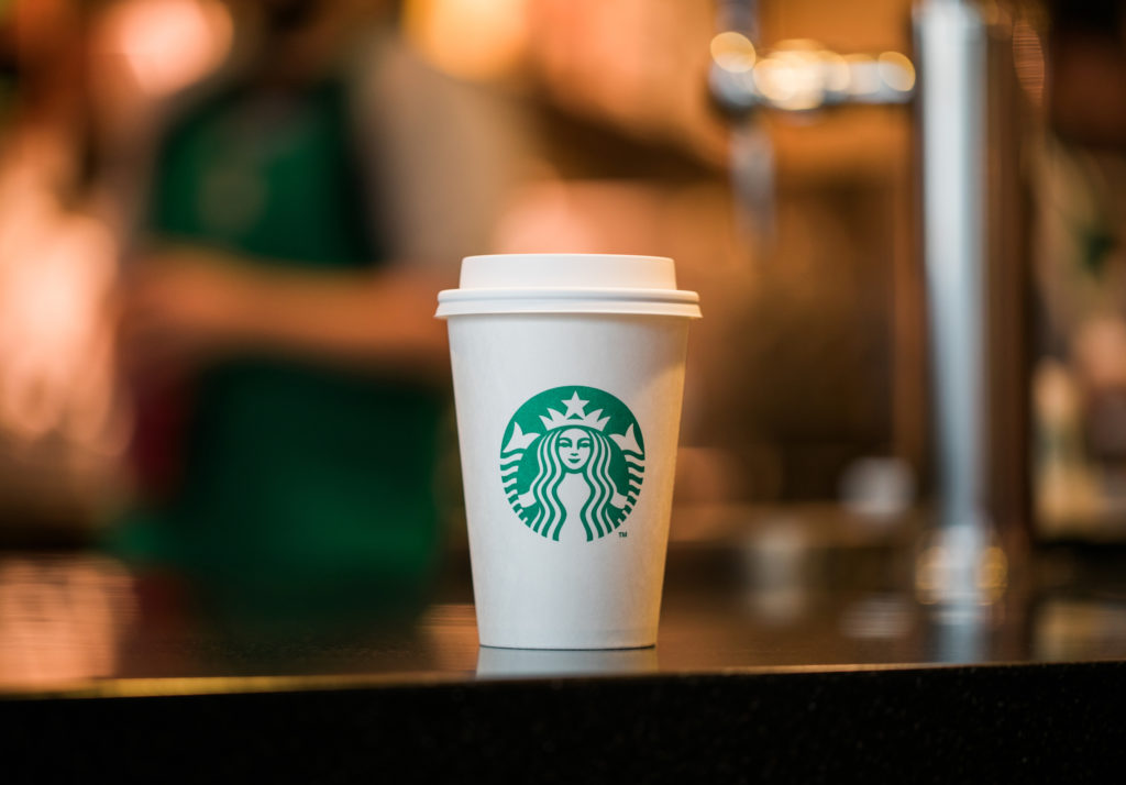 starbucks cup of company sitting on counter - companies with a cause