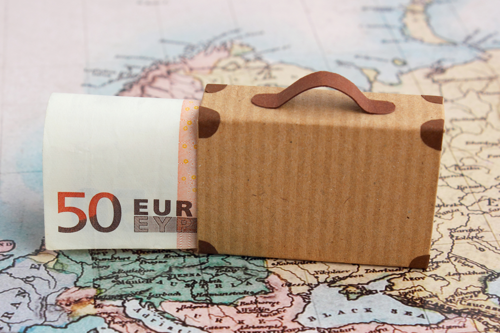 suit case and 50 euro sits on top of a map of Europe