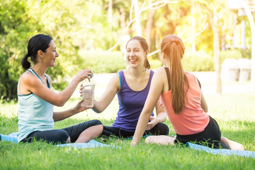 group of women sitting outside together after exercising.