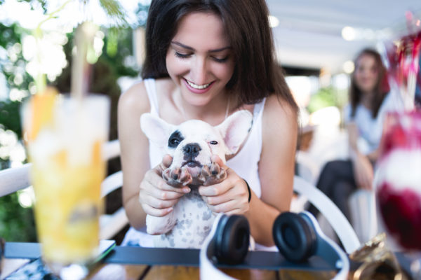 girl sitting with her dog at the table - meet my dog one of the best apps to make friends