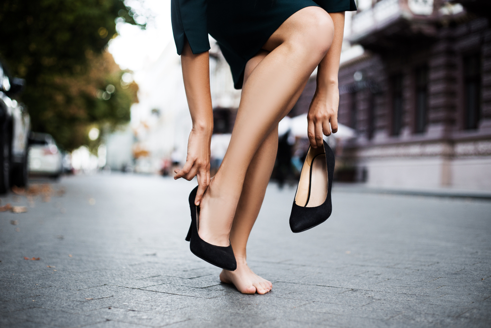 woman putting on high heels in preparation for reentering the workforce