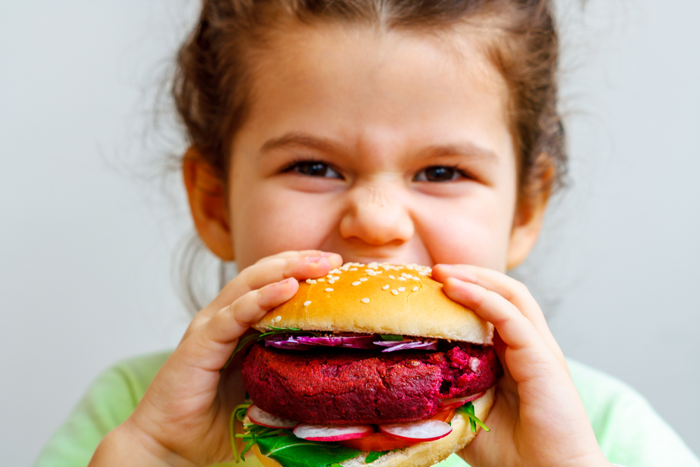 child raised vegan eating a vegan burger