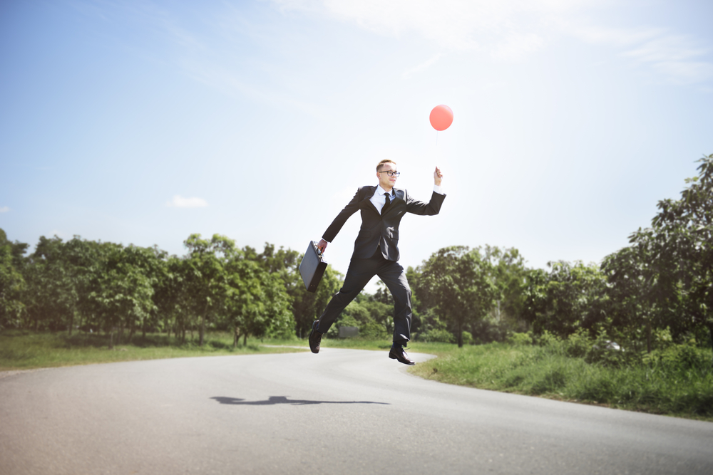 man in suit holding a balloon and floating to sky - symbolizing fun unusual jobs