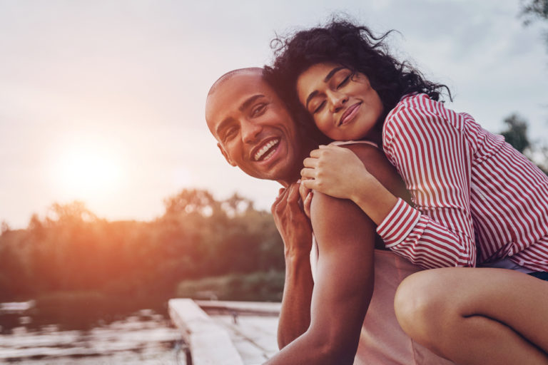 loving couple enjoying a sunset –strengthening positive relationships and improving personal wellness